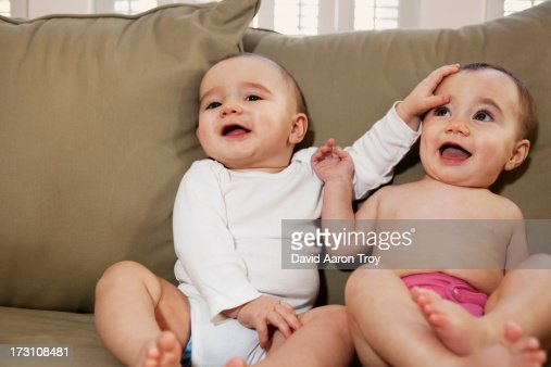 Twin brother and sister on a couch smiling : Stock Photo