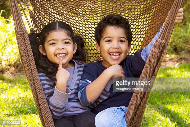 Twin brother and sister sitting in a hammock pulling funny faces