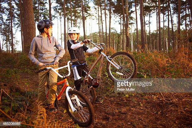 Twin brothers holding BMX bikes chatting in forest