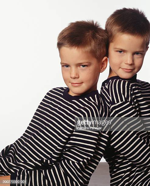 Twin brothers sitting back to back, posing in studio, portrait