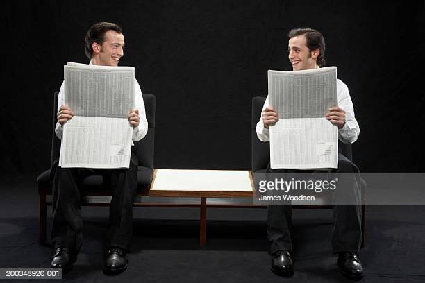 Twin brothers sitting, holding newspapers, smiling at each other