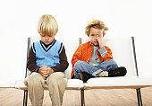 Twin brothers (3-5) sitting on chair, one praying