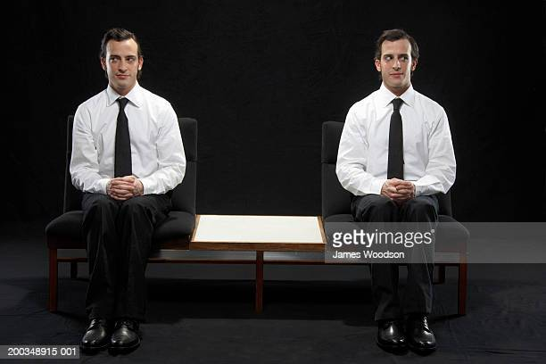 Twin brothers sitting on chairs, wearing suits