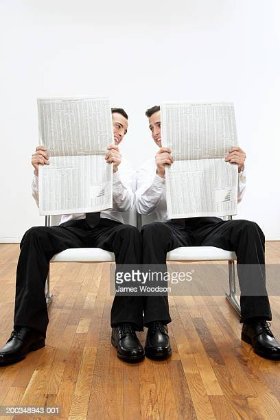 Twin brothers sitting side by side, holding newspapers
