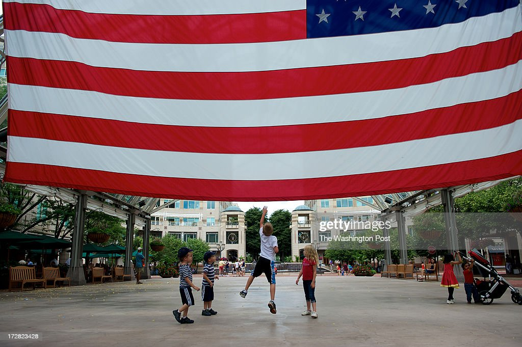 Twin brothers Trevor, Trey along with older brother Liam O'Sullivan in white and Asta Smitt-Jeppesen in red play with a large US flag hanging at the Reston Town Center, in Reston, Va.