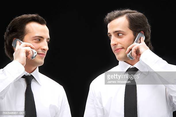 Twin brothers, using mobile phones, looking at each other, close-up