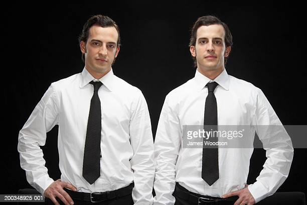 Twin brothers wearing suits, smiling, portrait