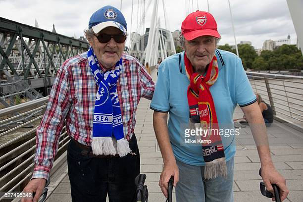 Twin brothers who support opposing football teams walking together across the Golden Jubillee Bridge next to Hungerford Bridge The brother on the...