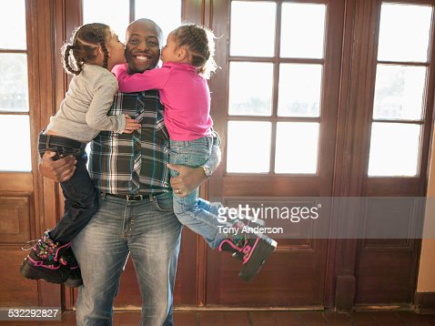Twin daughters hugging and kissing father