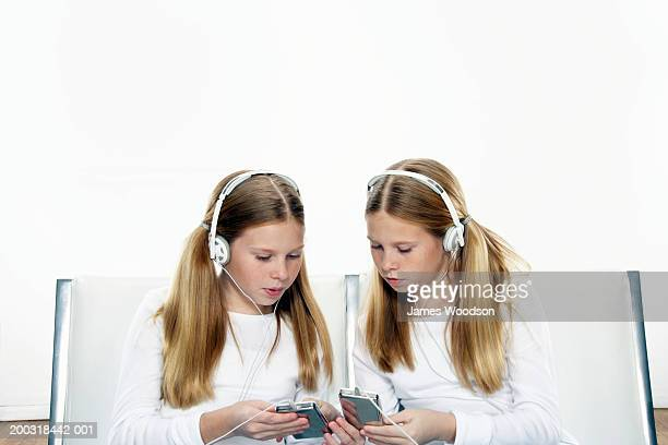 Twin girls (10-12) comparing MP3 players, close-up