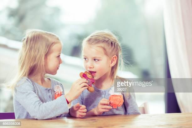 twin girls eating cookies
