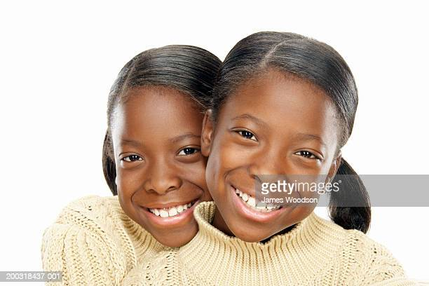 Twin girls (7-9) embracing, smiling, portrait, close-up
