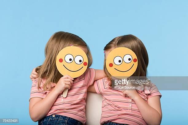 Twin girls holding face masks