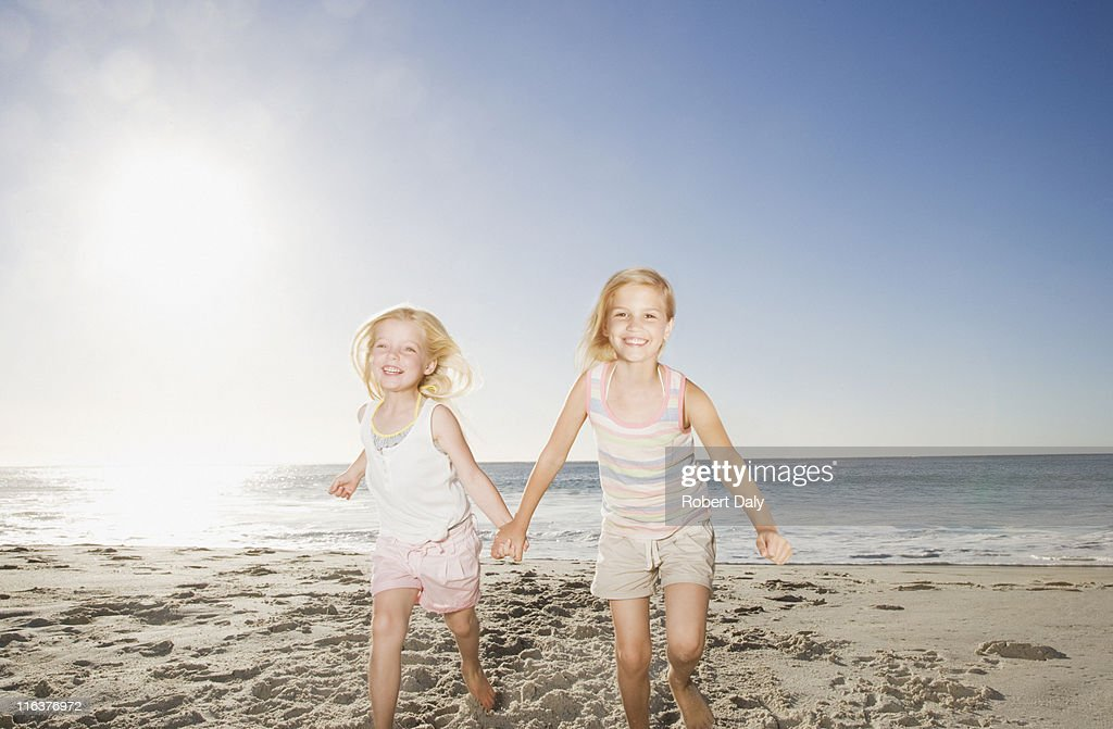 Twin girls holding hands on beach : Stock Photo