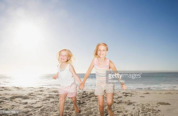 Twin girls holding hands on beach