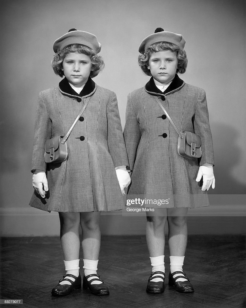 Twin girls in hats & coats wearing white gloves : Stock Photo