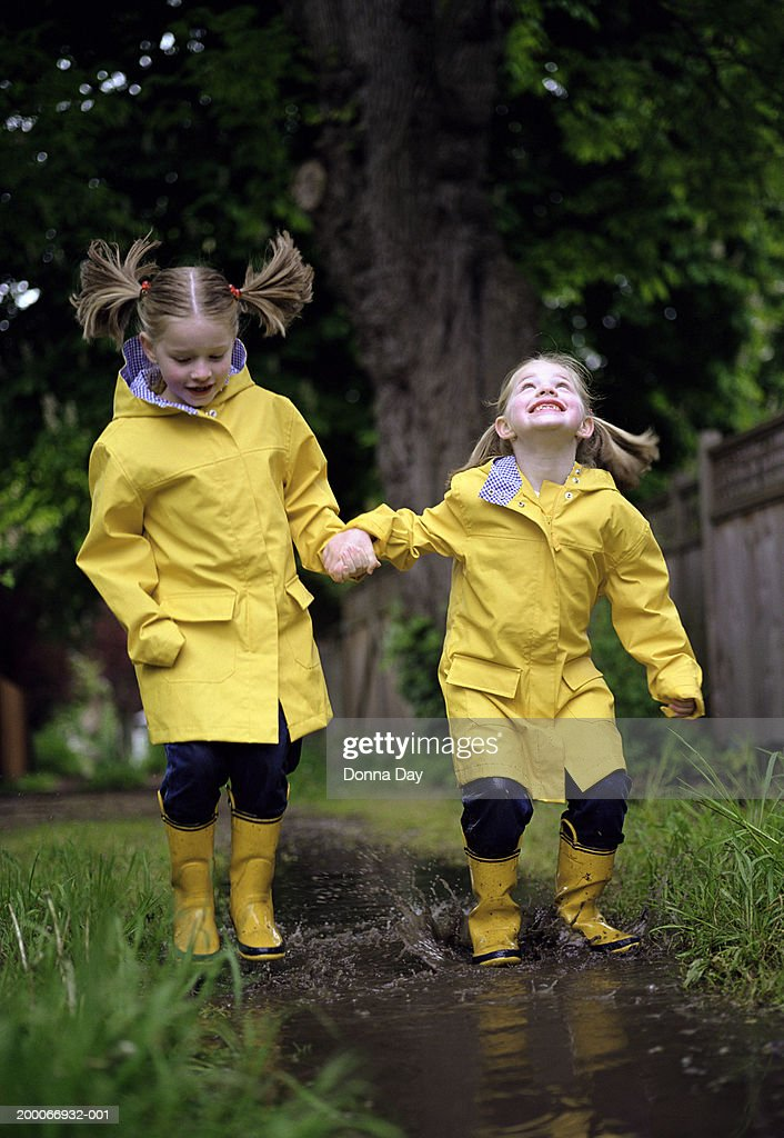 Twin girls (5-7) in raincoats and boots, jumping in mud puddle : Stock Photo