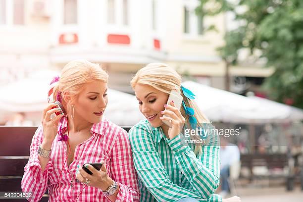 Zwei Mädchen im Rot und Grün mit Telefonen