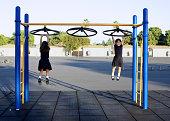 Twin girls playing on playground