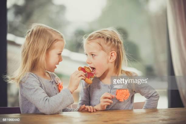 twin girls sharing cookies