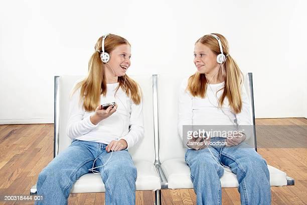 Zwei Mädchen (10-12) nebeneinander zuhören, MP3-Player, smilin