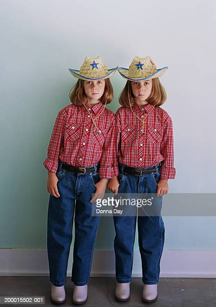 Twin girls (4-6) standing side by side in cowgirl costumes
