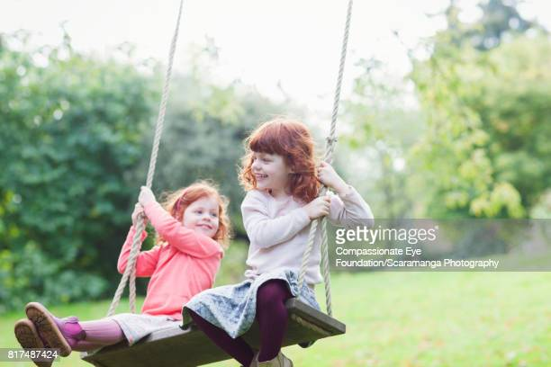 Twin girls swinging in backyard