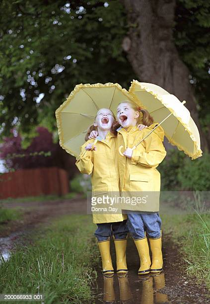 Twin girls (5-7) with matching raincoats, boots, and umbrellas singing