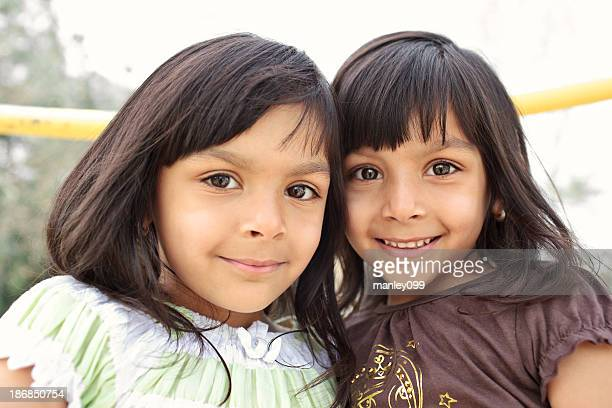 twin indian sisters smiling into camera