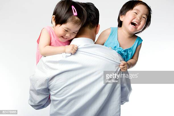 Twin kids peering over fathers arm and laughing