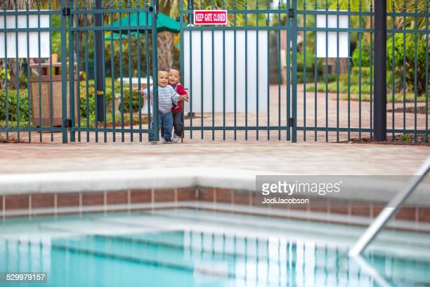 Twin little boys try to enter an unlocked swimming pool