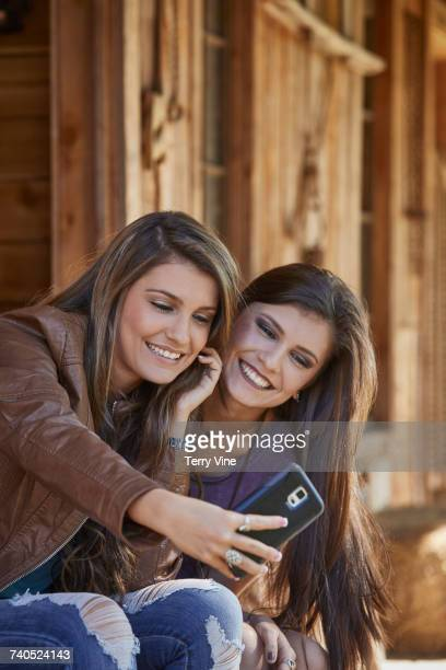 Twin Mixed Race teenage girls posing for cell phone selfie