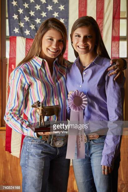 Twin Mixed Race teenage girls posing with awards near American flag