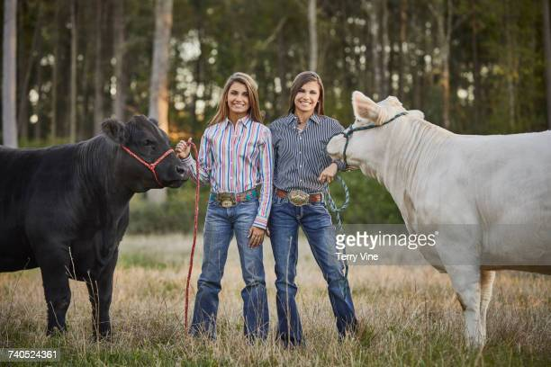 Twin Mixed Race teenage girls posing with cows in field