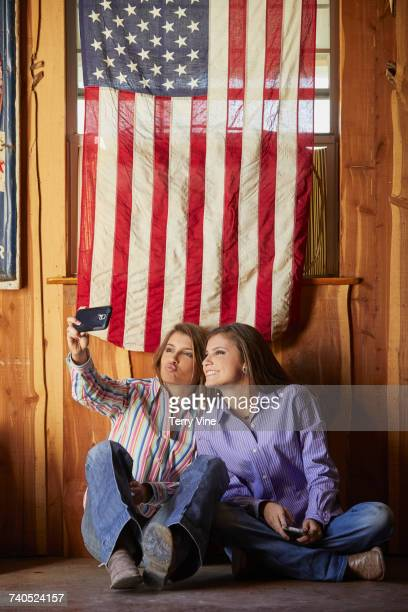 Twin Mixed Race teenage girls under American flag posing for selfie