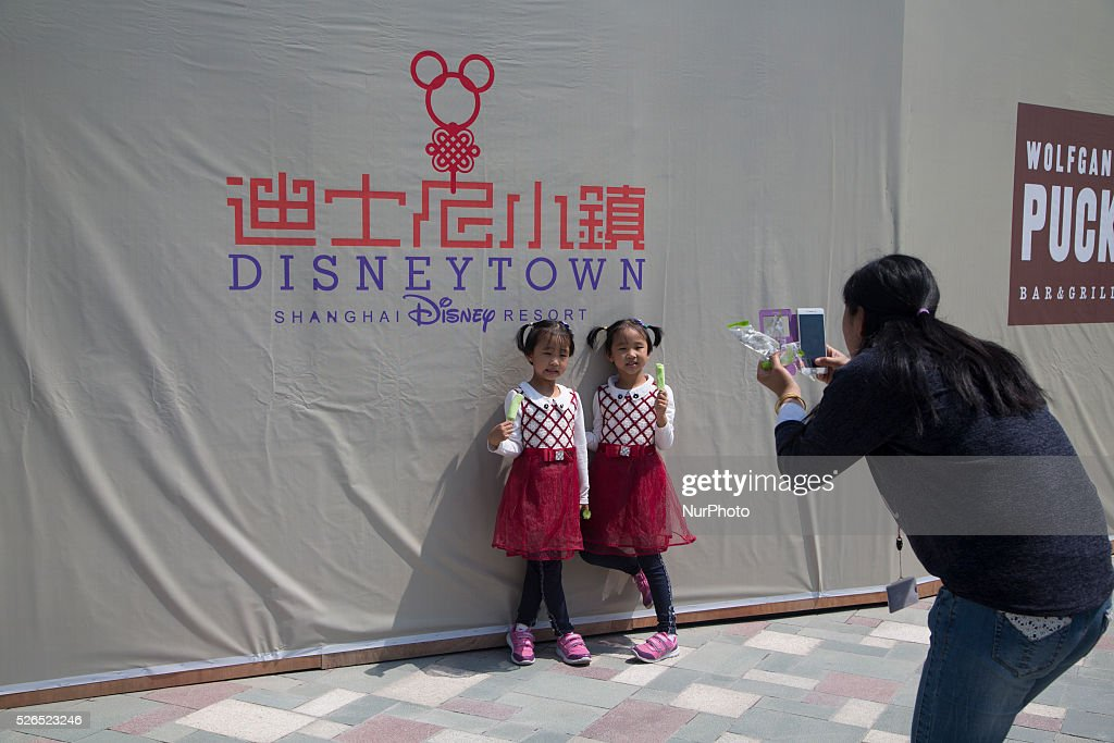Twin pose as their mother takes picture outside the Disney Town in Pudong District in Shanghai, China, Apr. 30 2016. Disneyland Shanghai still under costruction and has planned to open on June 16, 2016.