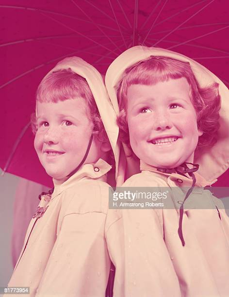 Twin red haired girls, wearing raincoats, sheltering under umbrella. (Photo by H. Armstrong Roberts/Retrofile/Getty Images)