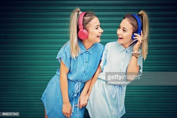 Deux sœurs jumelles sont à l'écoute la musique avec un casque sans fil et se moquer