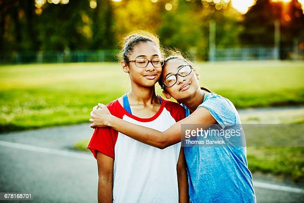 Twin sisters embracing on basketball court