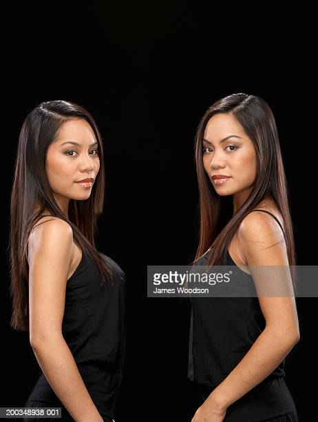 Twin sisters facing each other, portrait