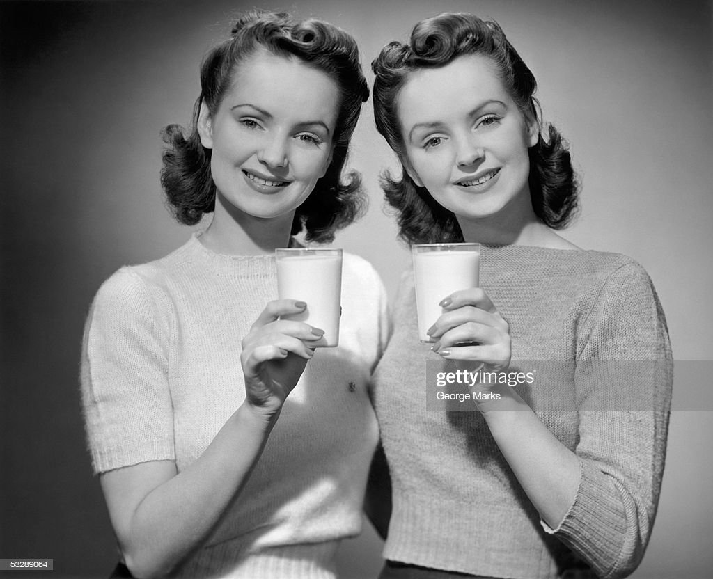Twin sisters holding glasses of milk : Stock Photo