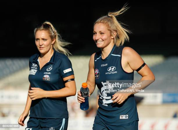 Twin sisters Jessica and Sarah Hosking of the Blues run back to the team during the 2017 AFLW Round 07 match between the Carlton Blues and the...