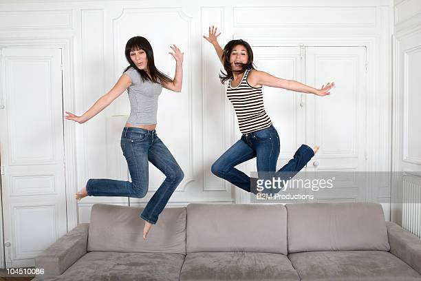 Twin sisters jumping on sofa.