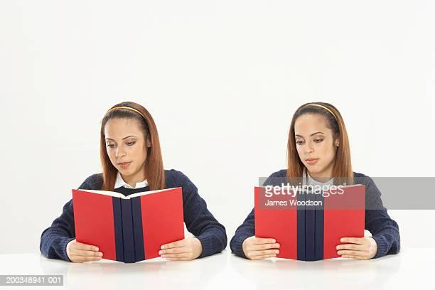 Twin sisters reading books, wearing school uniforms