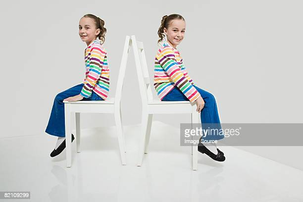 Twin sisters sitting on chairs