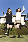 Twin sisters smiling and jumping in garden, front view