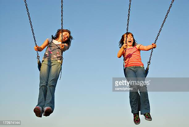 A twin sisters swinging happily on a sunny day
