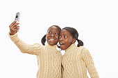 Twin sisters (7-9) taking self portrait with camera phone
