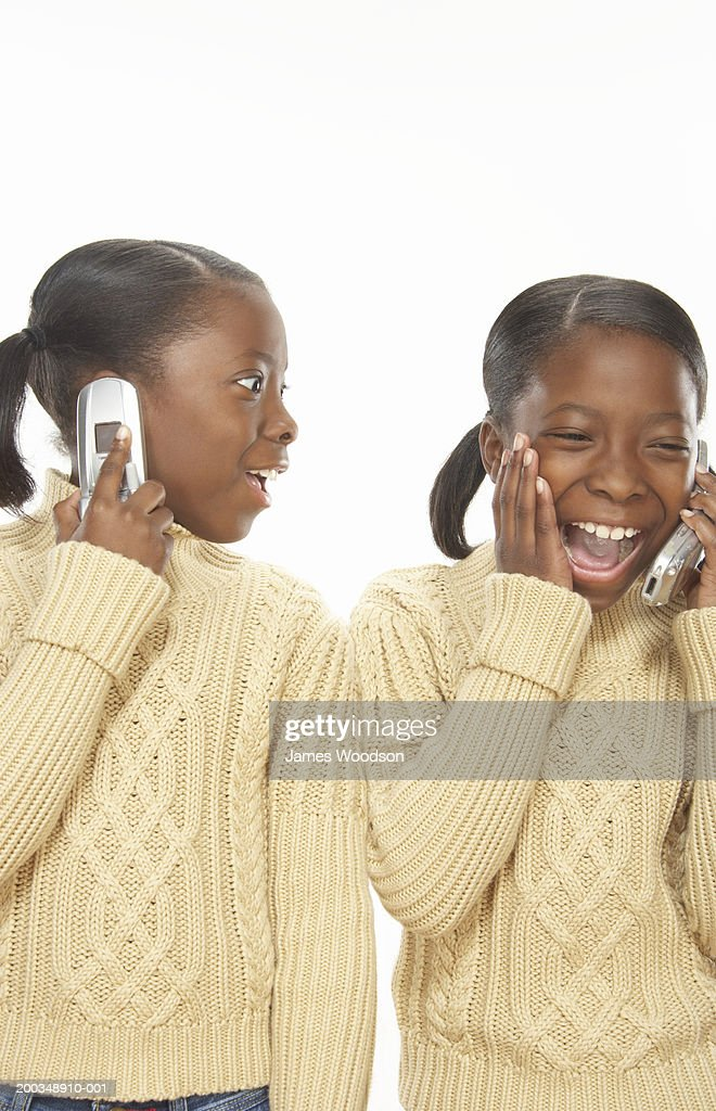 Twin sisters (7-9) talking on mobile phones, close-up : Stock Photo