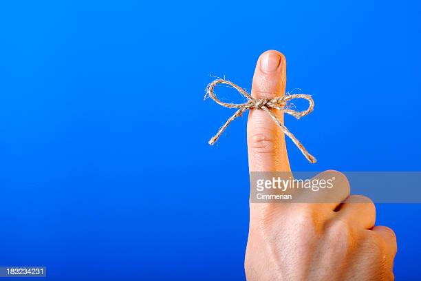 Twine tied in a bow around the pointed finger of kid's hand